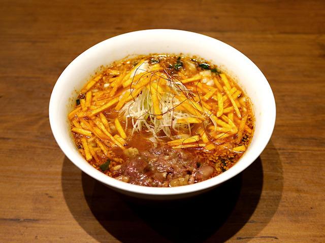 醤辛ムーチョ麺 牛骨らぁ麺 マタドール本店 使用スナック:スティックカラムーチョ ホットチリ味 スティックカラムーチョ にんにくチョモランマ ホットチリ味 限定数量:なし / 価格:900円  醤油をベースにした韓国風のピリ辛スープに、牛肉の旨みがギュッと詰まった一杯です。トッピングである『スティックカラムーチョ ホットチリ味』と『スティックカラムーチョ にんにくチョモランマ ホットチリ味』の 絶妙なバランスにより、スタミナ満点の一杯です。追いメシ付きで、最後はクッパとしてもお楽しみいただけます!
